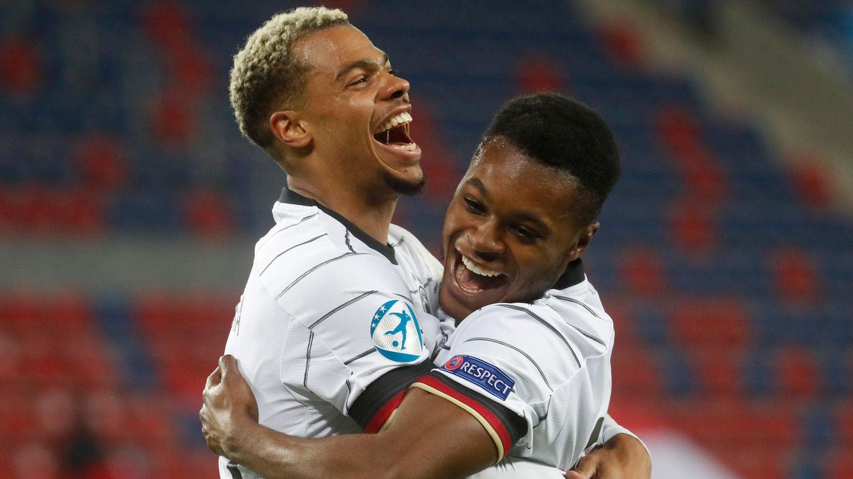 Zwei farbige junge Erwachsene in Trikots der deutschen Fußball-Nationalmannschaft liegen sich jubelnd in den Armen