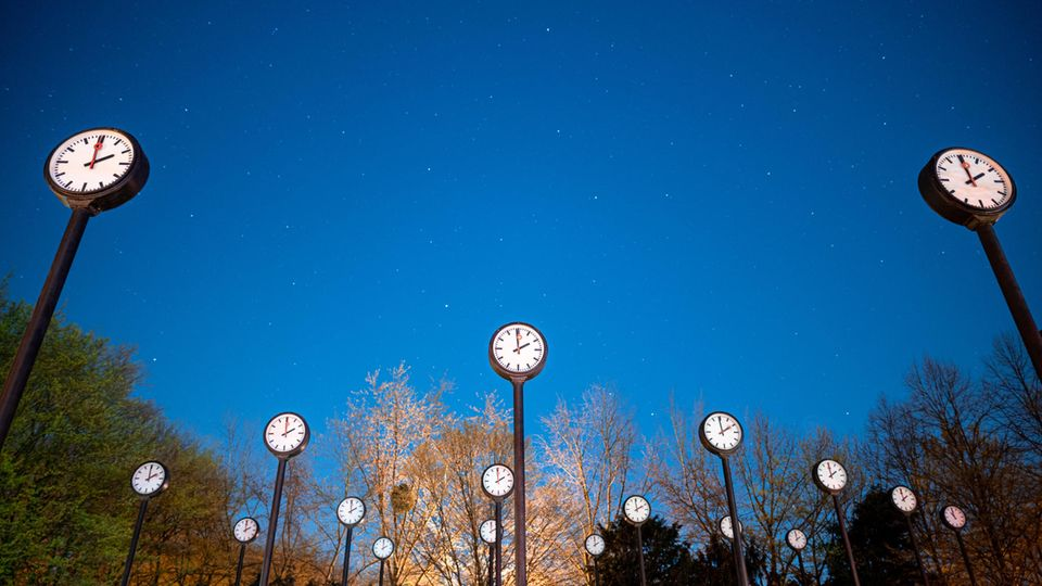 Mehrere große Uhren mit weißem Zifferblatt und schwarzen Zeigern stehen im Freien