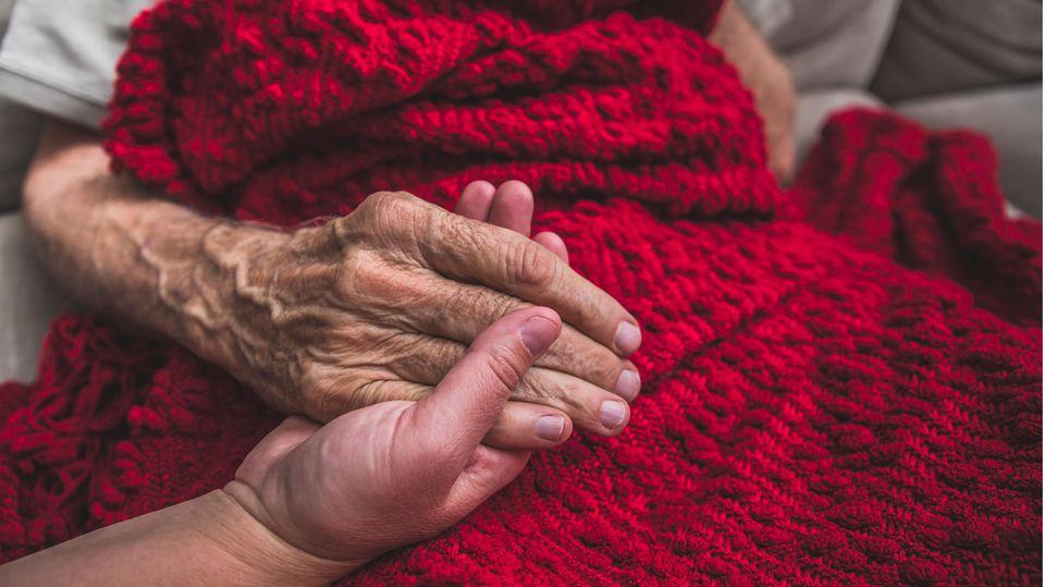 Krankenschwester in einem Hospiz hält einem Sterbenden die Hand