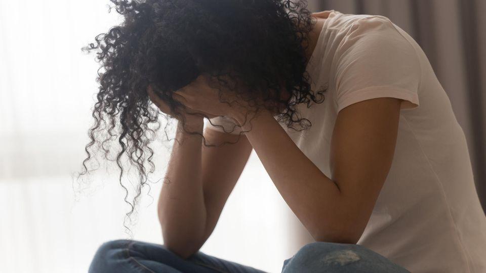 Eine trauernde Frau sitzt auf dem Bett