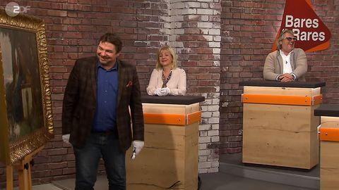 Daniel Meyer steht im Bares für Rares Händlerraum, Elke Velten-Tönnies und Roman Runkel sitzen daneben