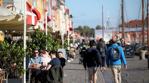 Menschen sitzen draußen in Restaurants und Cafés in Nyhavn, Kopenhagen
