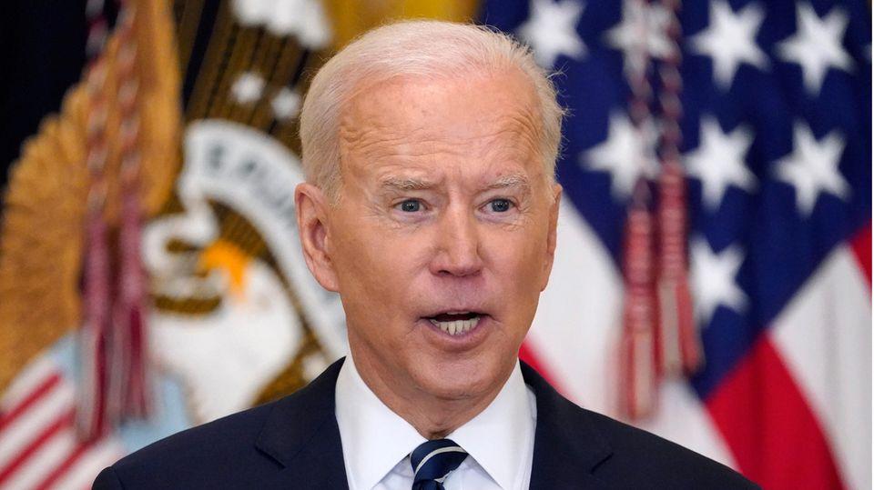 US-Präsident Joe Biden spricht, während hinter ihm unscharf US-Flaggen zu sehen sind