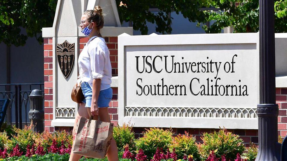 """Eine junge Frau vor einem Schild mit der Aufschrift """"University of California"""""""