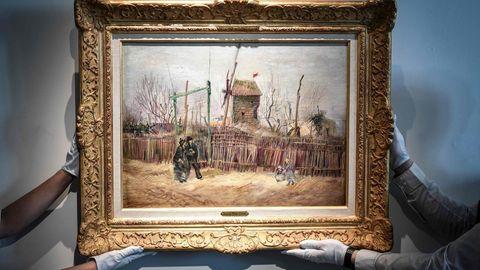 """Mitarbeiter des Auktionshauses Sotheby's halten mit behandschuhten Händen das Gemälde """"Scène de rue à Montmartre"""""""