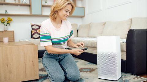 Luftkühler im Wasser: Junge Frau sitzt am Tisch vor einer Mini-Klimaanlage