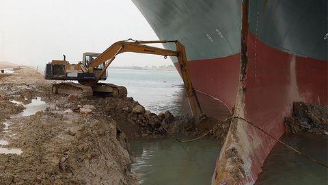 """Ein Bagger schaufelt am Frachter """"Ever Given"""", der im Suezkanal auf Grund gelaufen ist und feststeckt"""