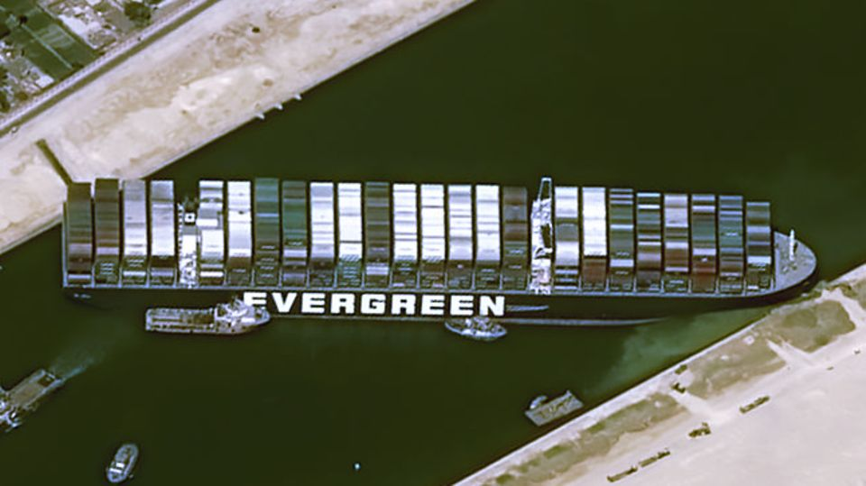 """Wie eine Brücke liegt die """"Ever Given"""" zwischen West- und Ostufer des Suezkanals verkeilt"""