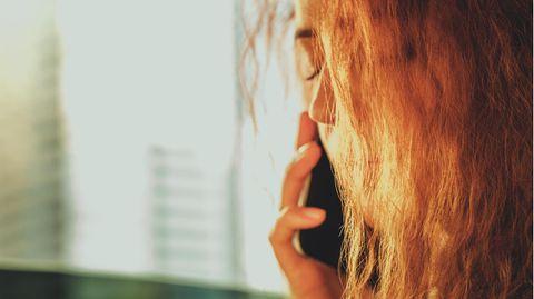 Frau schließt die Augen, während sie telefoniert
