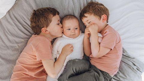 Drei Geschwister liegen auf einem Bett