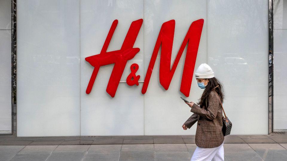 Eine Frau geht am Flagshipstore der Bekleidungsmarke H&M in einer Einkaufszone in Peking vorbei