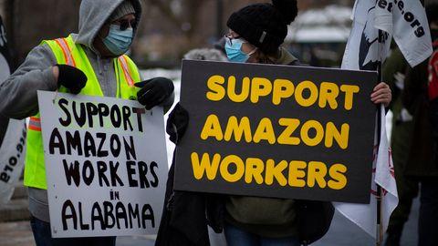Zwei Personen demonstrieren mit Schildern für die Rechte von Amazon-Mitarbeitenden