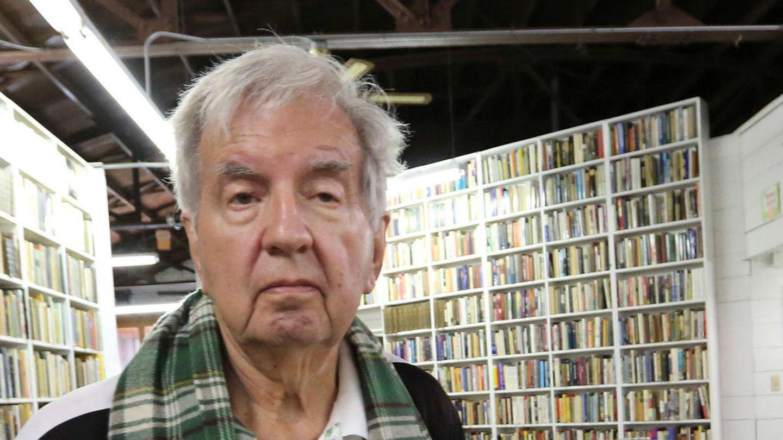 Ein weißhaariger Mann steht in Sportjacke und grünkariertem Schal in einer Buchhandlung mit vollen Wandregalen