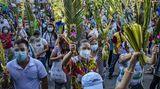 Manila, Philippinen.Mit Maske und Gesichtsschutz aus Plexiglas begehen in den katholisch geprägten Philippinen die Menschen den Sonntag vor Ostern. Am letzten Sonntag in der Fastenzeit, auch Palmarum genannt, halten die Gläubigen frische Palmenzweige in die Höhe.