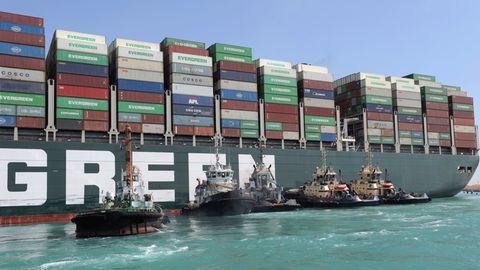 Fünf Schlepper schieben am Heck eines riesigen Containerfrachters