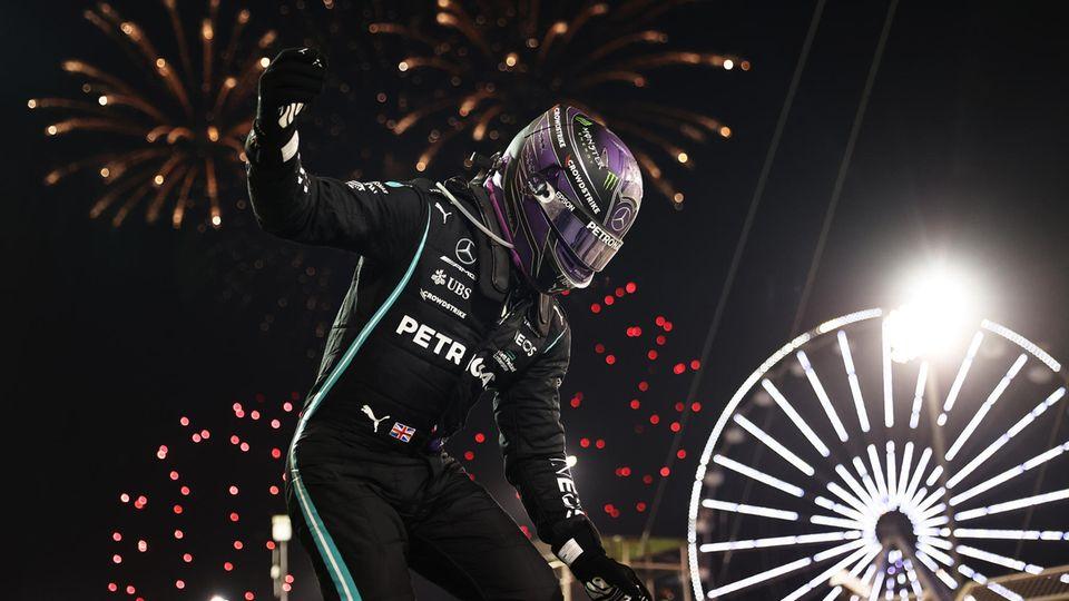 Lewis Hamilton springt unmittelbar nach dem Rennen ausseinem Auto, während ein Feuerwerk den Himmel über Bahrain erhellt