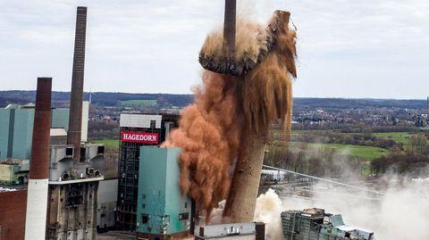 Ein gemauerter Schornstein sackt nach einer Sprengung in drei Teilen und einer Staubwolke zusammen