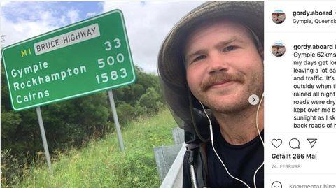 Ein junger Mann steht vor einem Straßenschild in Australien