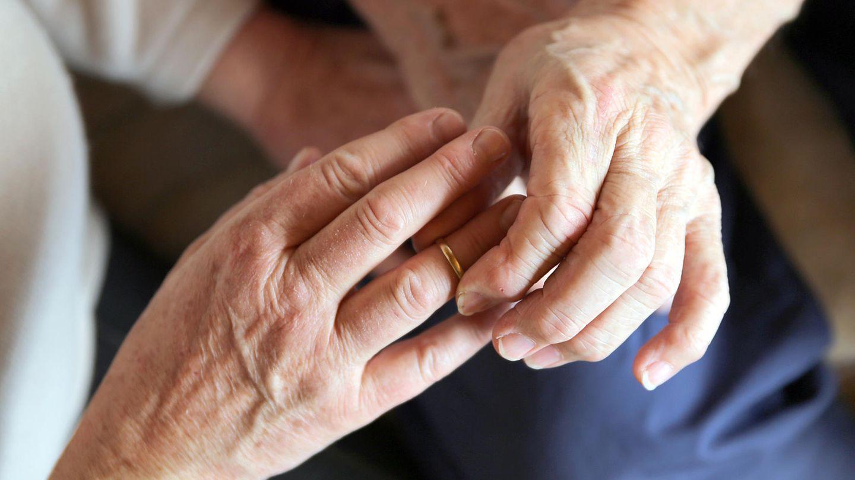Älterer Mann steckt Ring an Finger von älterer Frau.