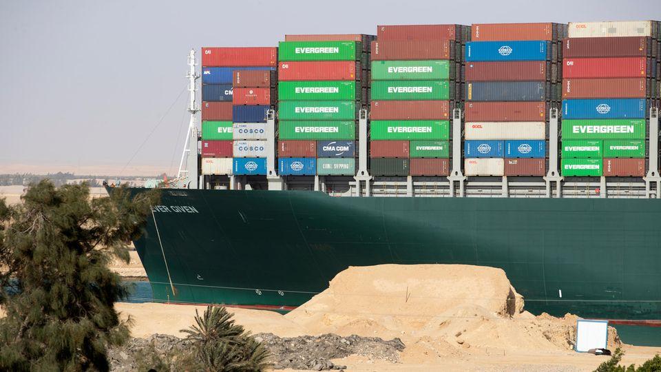 """Von einem flachen Hausdach aus beobachten zwei Männer, wie die """"Ever Given"""" auf dem Suezkanal wieder Fahrt aufnimmt"""