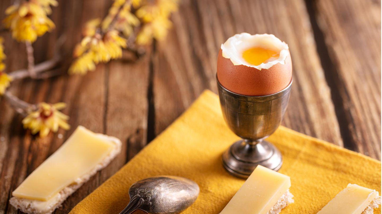 Frühstückstisch mit Käsebroten und einem weich gekochten Ei im Becher