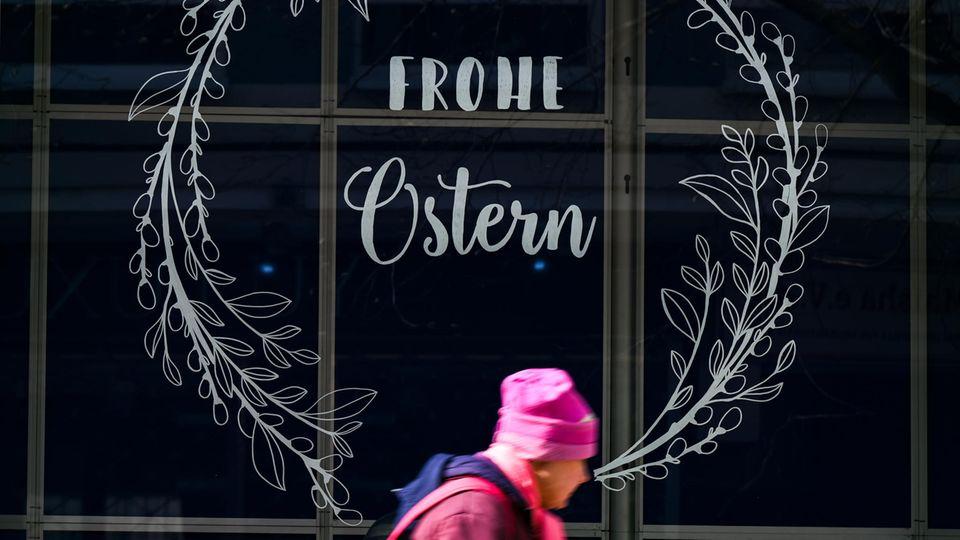 Eine Frau geht in der Frankfurter Innenstadt am Schaufenster eines Modegeschäfts vorbei
