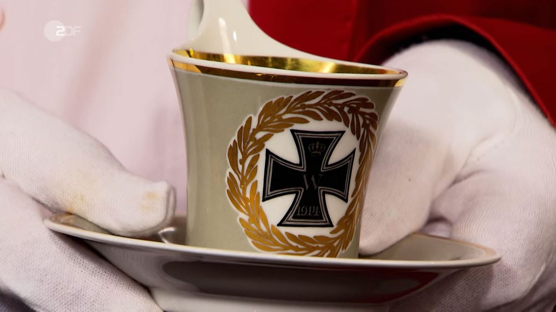 Experte Albert Maier hebt die skurrile Tasse aus dem Ersten Weltkrieg in die Kamera