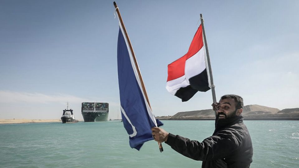 """Ein Arbeiter schwenkt eine Flagge Ägyptens, im Hintergrund das Containerschiff """"Ever Given"""""""