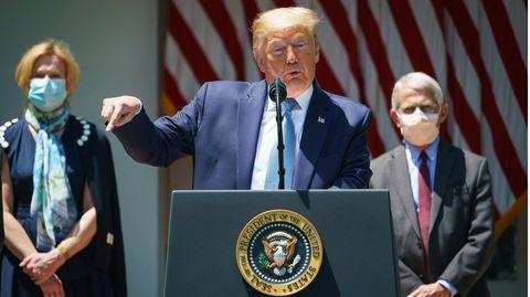 Donald Trump spricht, im Hintergrund Fauci und Birx