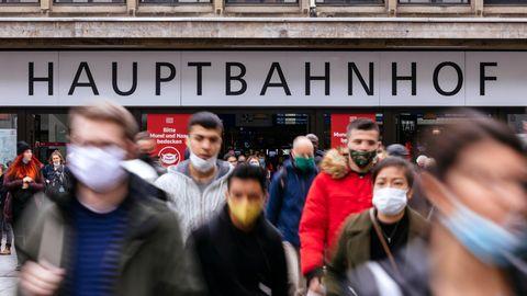 """Am Düsseldorfer Hauptbahnhof fordern Schilder der Deutschen Bahn Reisende dazu auf: """"Bitte Mund und Nase bedecken"""""""