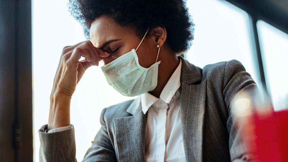 Eine Frau mit Mund-Nase-Schutz hält sich erschöpft an die Nase