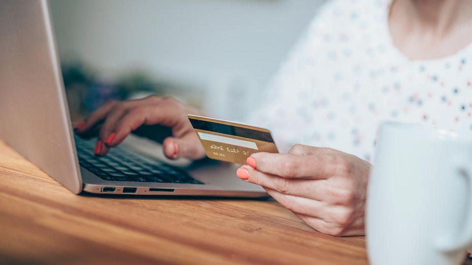 Symbolbild zum Thema Romance Scamming: Eine Frau sitzt mit Kreditkarte vor einem Rechner