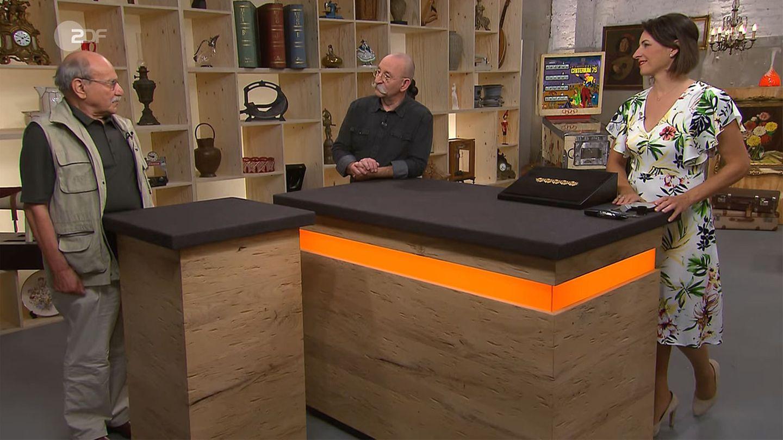 Verkäufer, Moderator Horst Lichter und Wendela Horz stehen am Tresen im Bares für Rares Studio in Pulheim