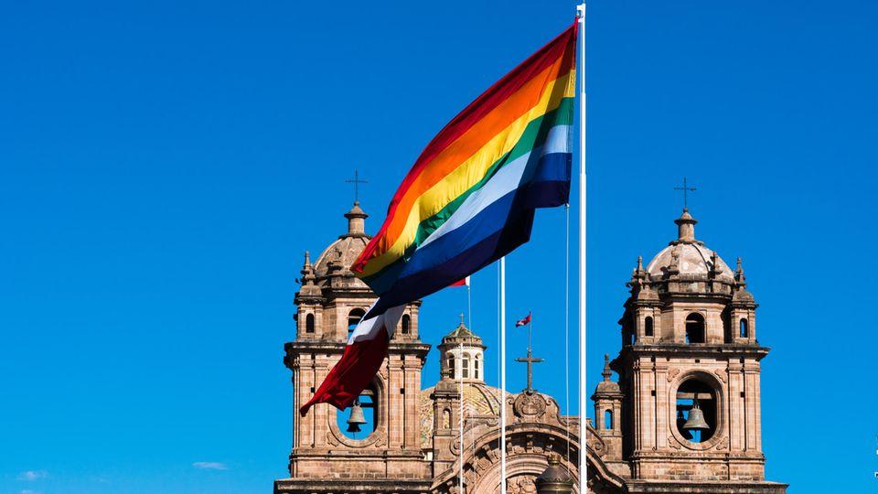 Regenbogenflagge weht vor Kirchturm