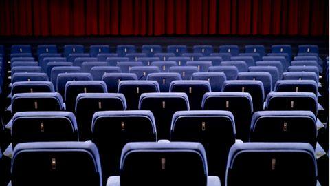 Leerer Kinosaal vor rotem Vorhang.
