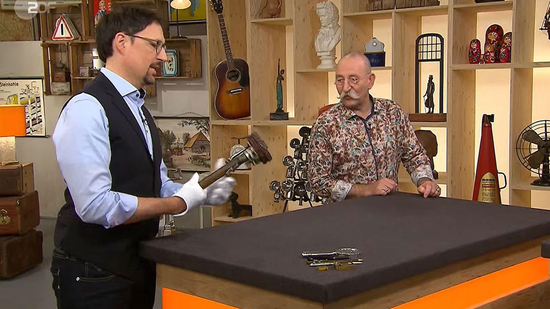 Colmar Schulte-Goltz und Horst Lichter bestaunen im Bares für Rares Studio in Pulheim das ungewöhnliche Objekt.