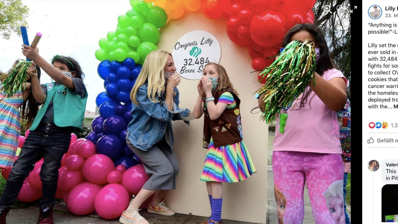 Kinder und Mütter feiern vor einer bunten Wand, auf der das Verkaufsergebnis enthüllt wurde