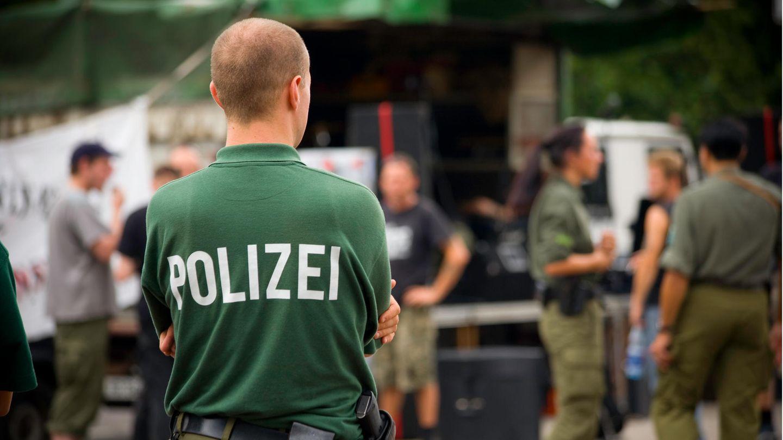 Ein Beamter mit Polizei-Shirt steht auf einem Hof