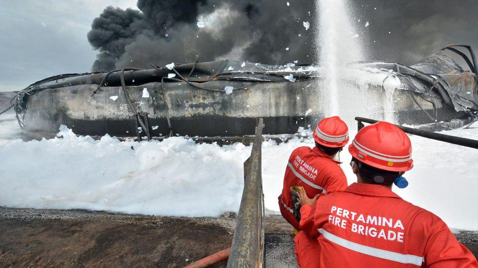 Zwei Feuerwehrleute in roten Uniformen und Helmen spritzen Schaum auf die verrußten Trümmer einer Ölraffinerie mit Rauchfahne