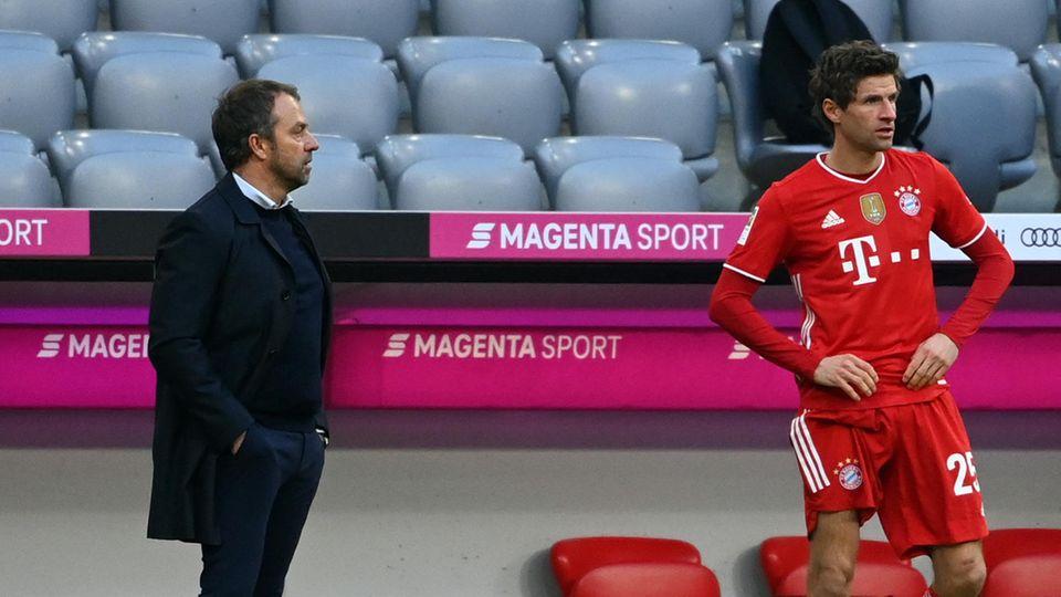 Münchens Thomas Müller (r.) steht neben Trainer Hansi Flick zur Einwechslung bereit