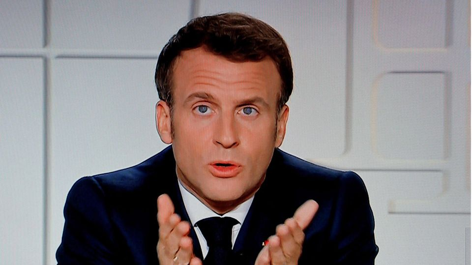 Frankreichs Präsident Macron sitzt in einem TV-Studio vor weißem Hintergrund und zeigt mit beiden Händen auf die TV-Zuschauer