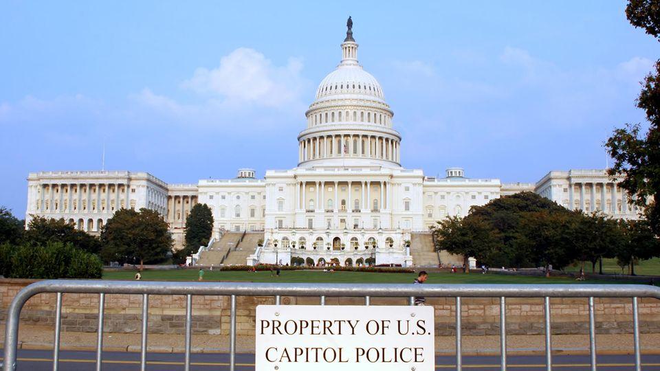 Das US-Kapitol in Washington D.C. aus der Ferne, vorne steht eine Polizeiabsperrung