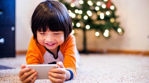Junge spielt auf einem Smartphone.