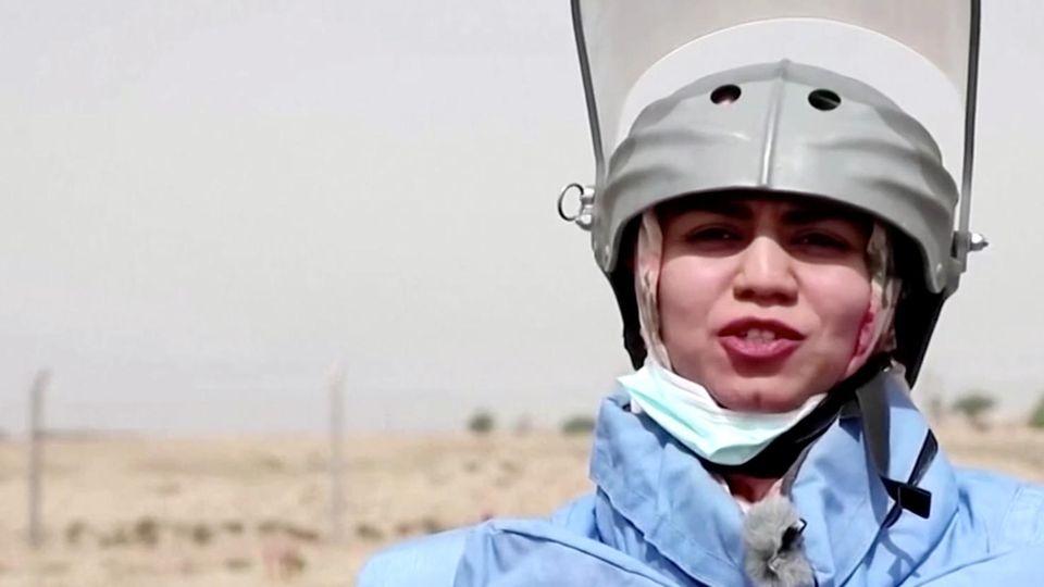 Eine Frau steht in hellblauer Sprengmeister-Schutzausrüstung im Freien in der Sonne