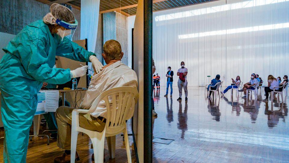 Ein Mitarbeiter des Gesundheitswesens verabreicht einem älteren Herrn den Impfstoff von Astrazeneca