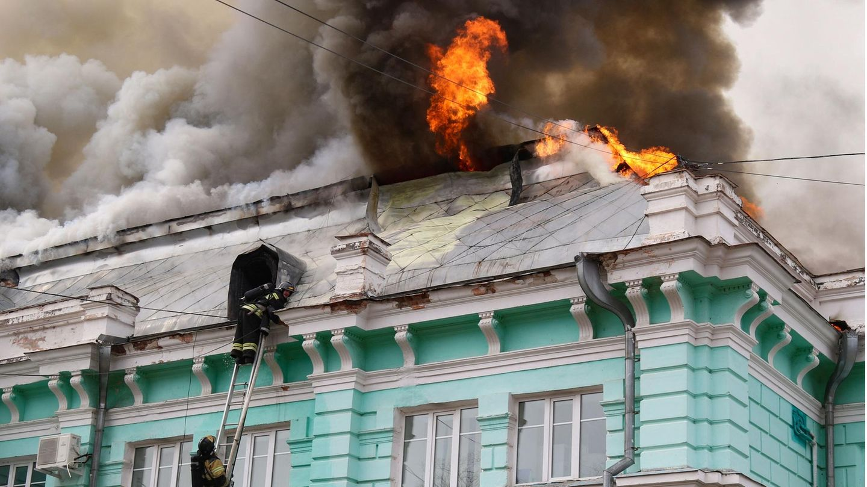 Während aus dem Dach eines mintgrünen Altbaus Flammen schlagen, erklimmen zwei Feuerwehrleute eine Leiter an der Außenfassade