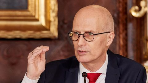 In blauem Anzug und roter Krawatte zeigt ein glatzköpfiger Mann mit Brille mit der rechten Hand ein Niveau an