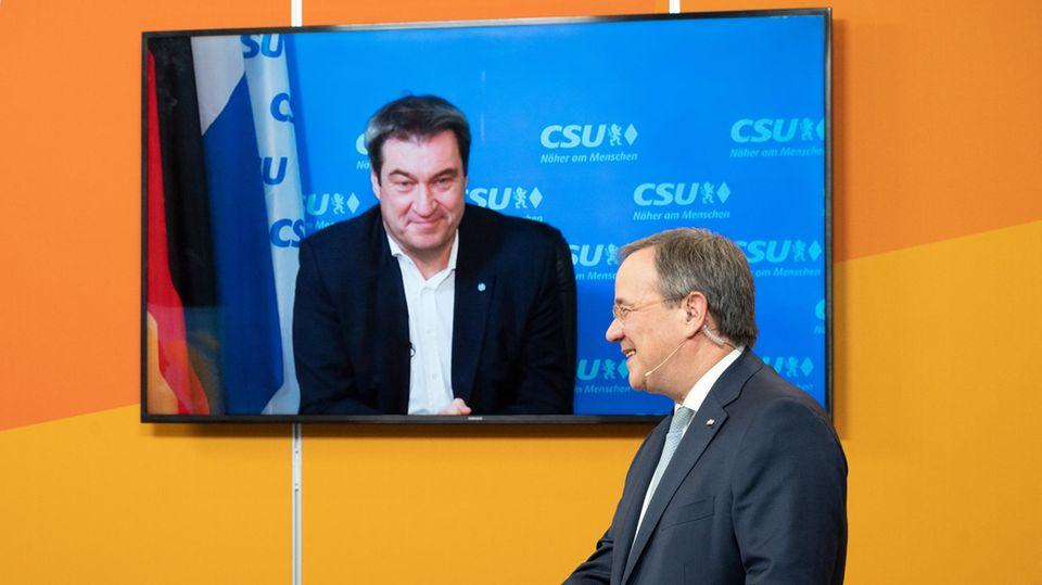 Der CDU-Parteivorsitzende Armin Laschet steht im Anzug an einem Rednerpult mit CDU-Logo, ein TV-Gerät im Hintergrund zeigt Söder