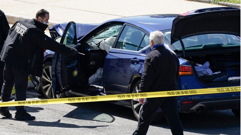 """Ein Mann der """"U.S. Capitol Police"""" steht an der geöffneten Fahrertür eines blauen BMW. Die Frontscheibe ist zersplittert"""
