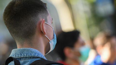 Ein Jugendlicher mit ausrasiertem Nacken ist von hinten zu sehen. Er trägt eine OP-Maske. Im Hintergrund stehen Altersgenossen
